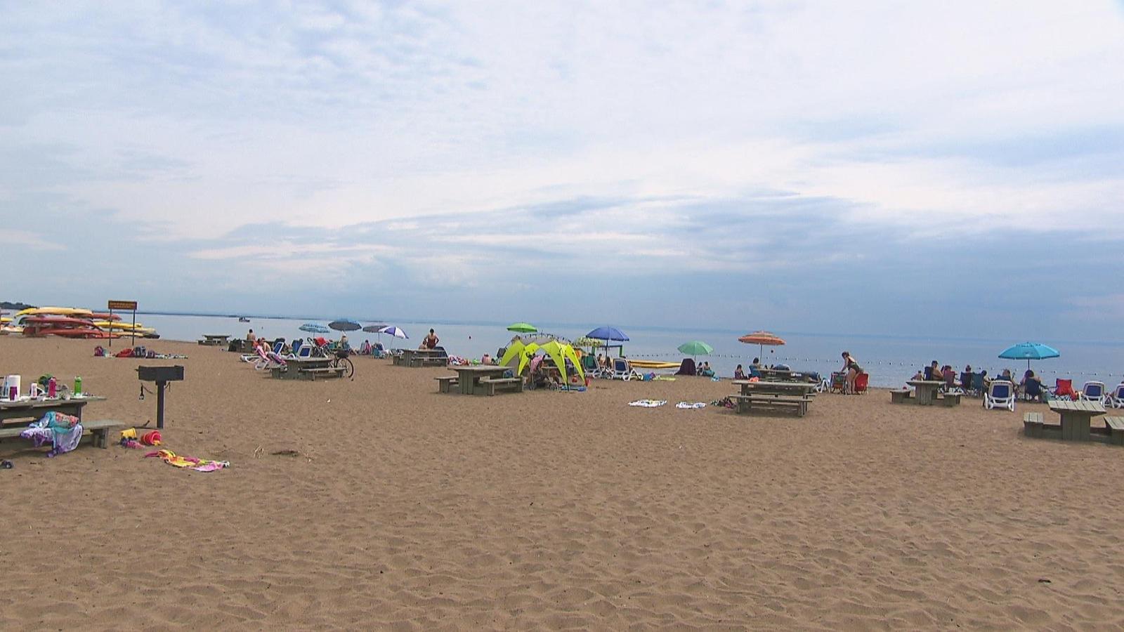 Plusieurs personnes se trouvent sur une longue plage. On peut voir le lac Saint-Jean en arrière plan.