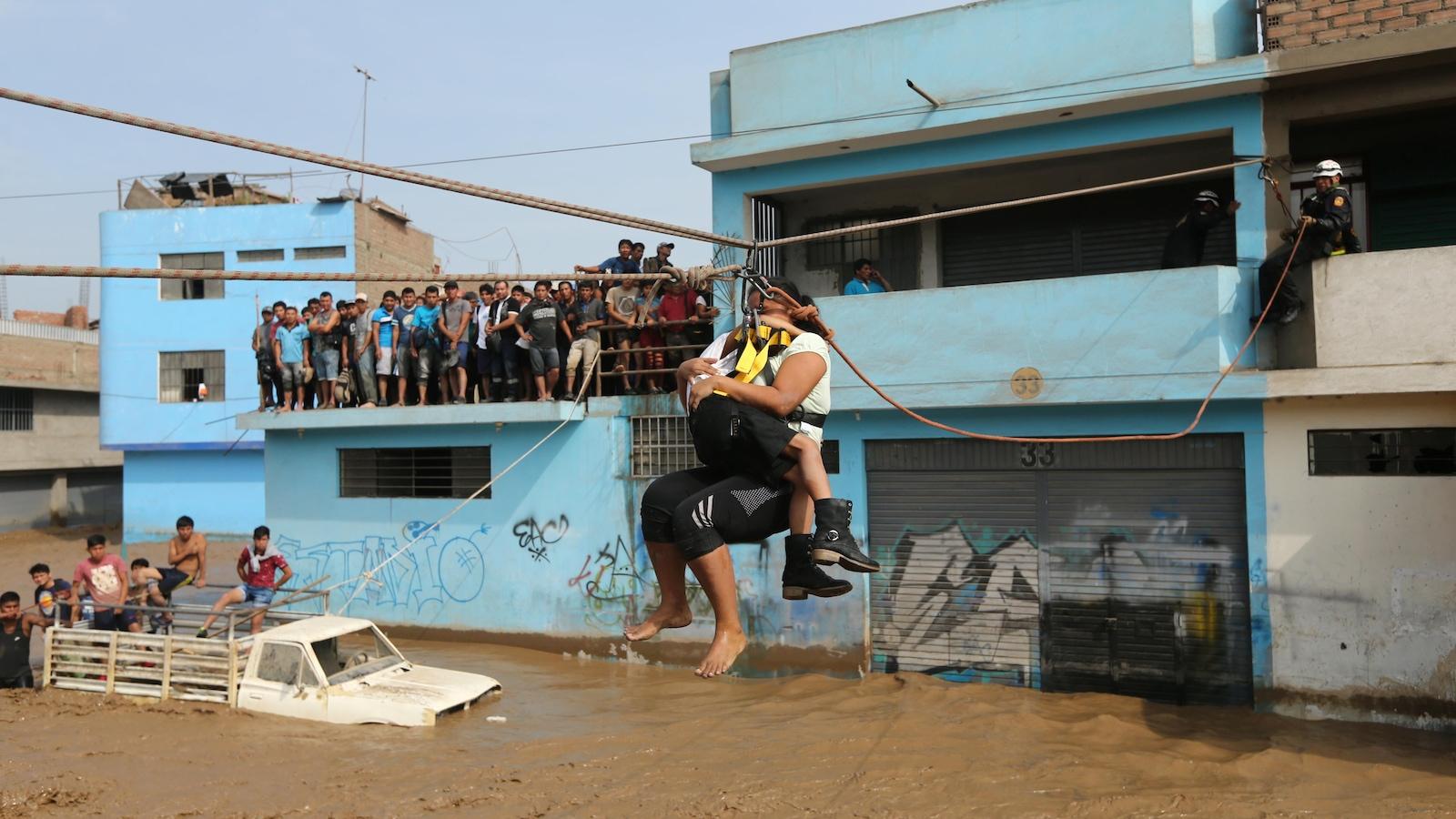 Une femme et son enfant traversent un fleuve en crue grâce à une tyrolienne installée par des secouristes