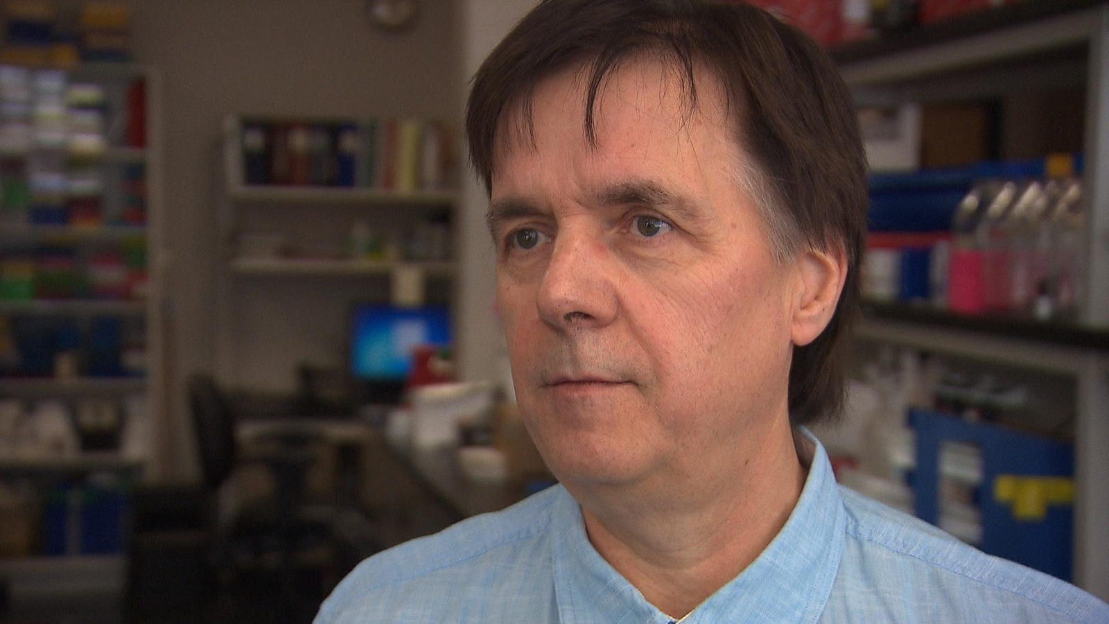 Un homme dans un laboratoire de recherche regarde un journaliste lors d'une entrevue.