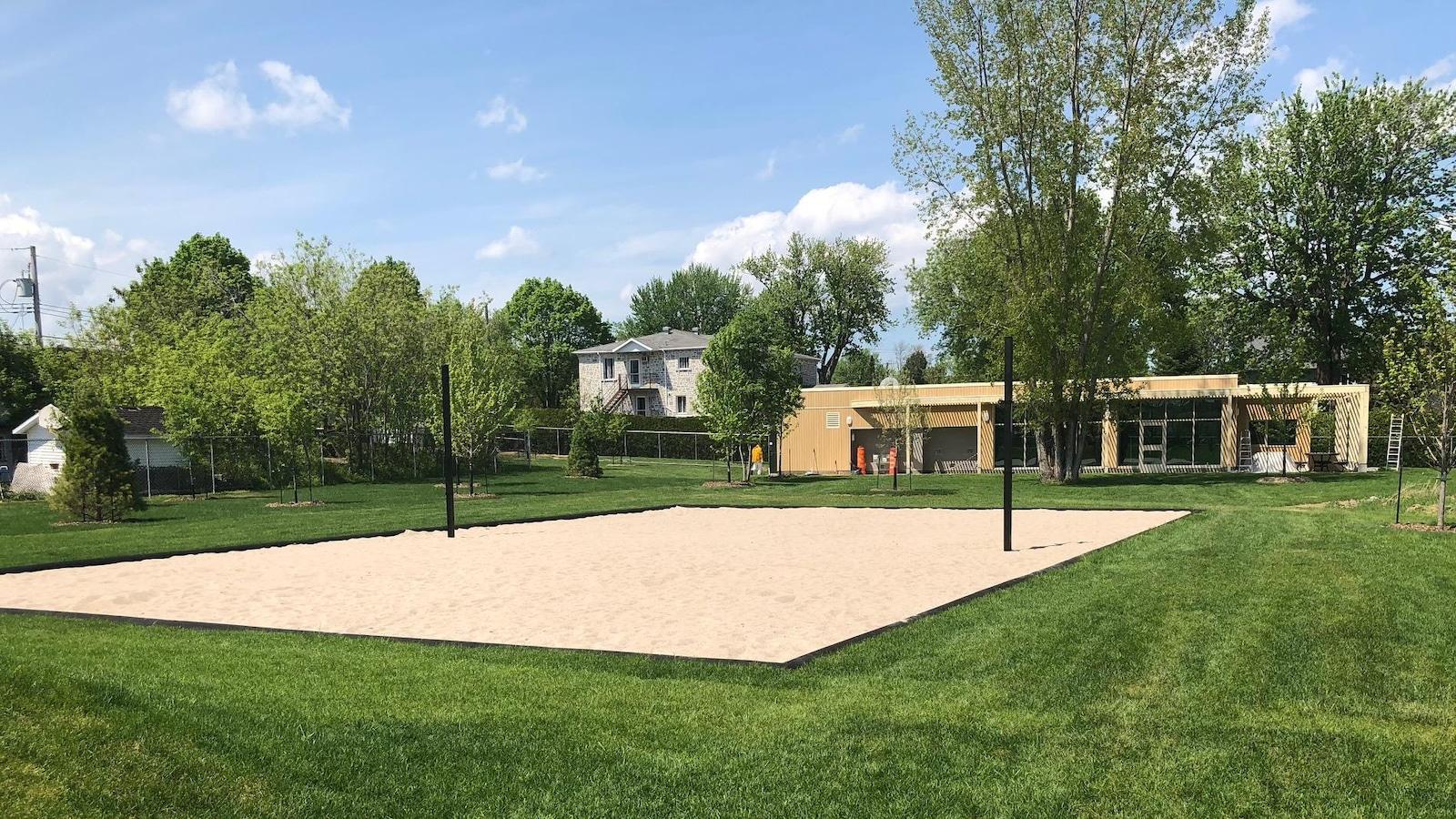 Pelouse sur laquelle se trouvent le terrain de volleyball et le chalet