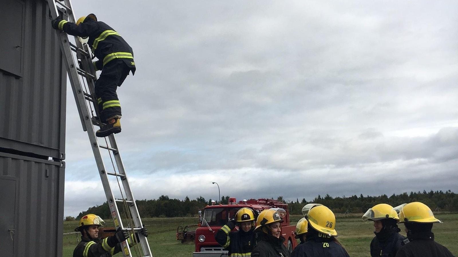 Une pompière d'un jour monte dans une échelle à Mont-Joli.