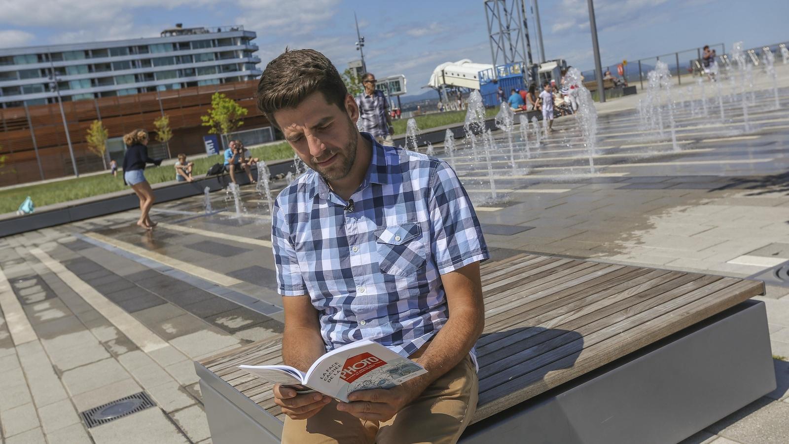 Au centre d'une photo, un homme qu'on voit de face lit un livre. Il faut son autorisation pour publier