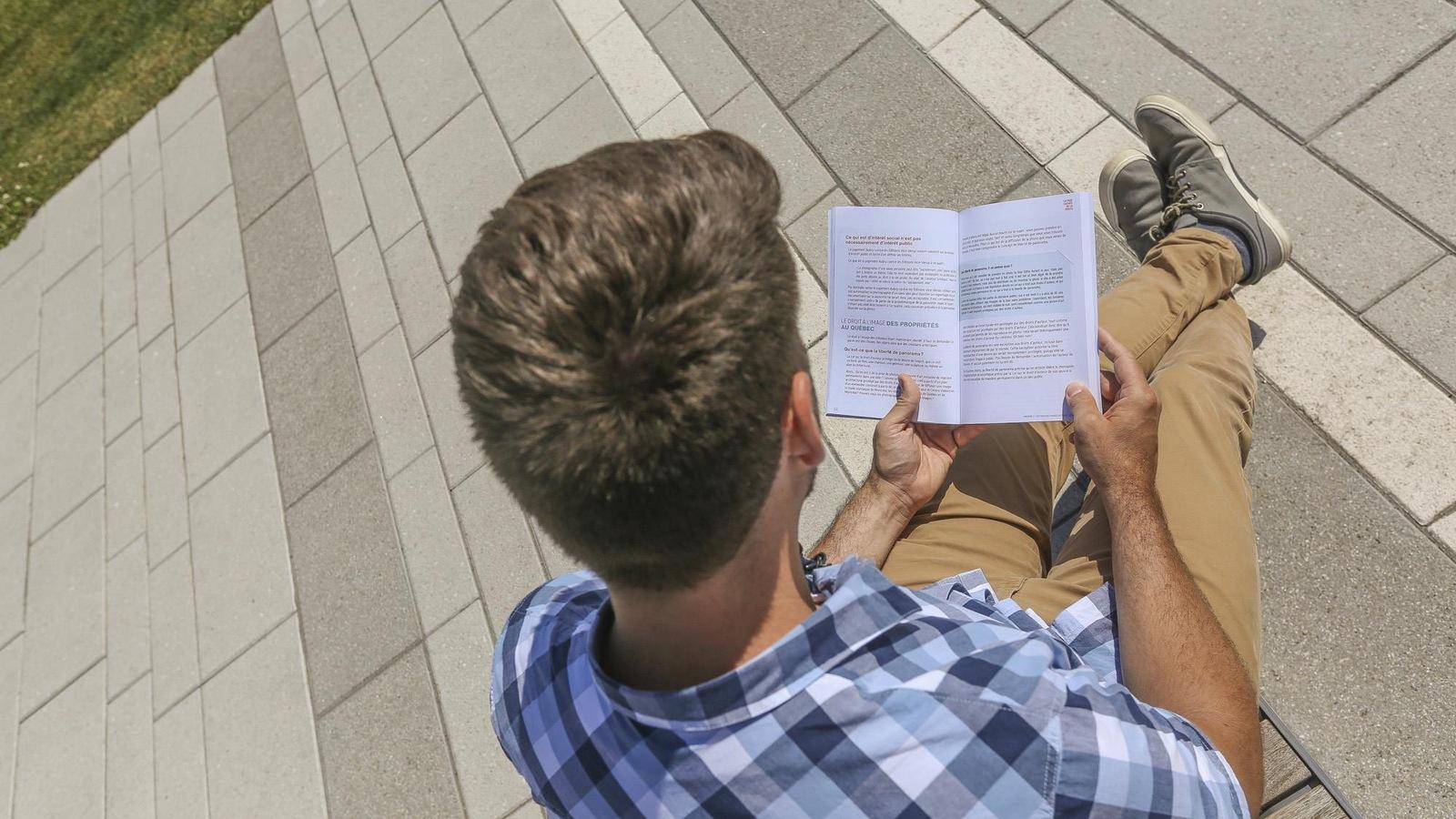 La photographie montre un homme lisant de dos et difficile à identifier. Il n'est pas nécessaire d'obtenir son consentement pour publier.