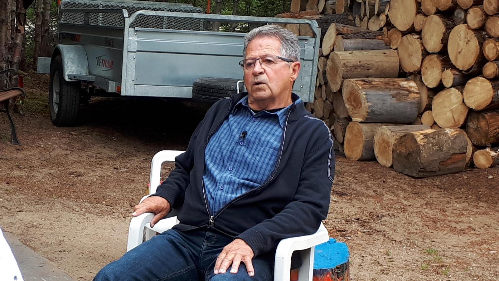 René-Claude Girard assis à l'extérieur dans son camping