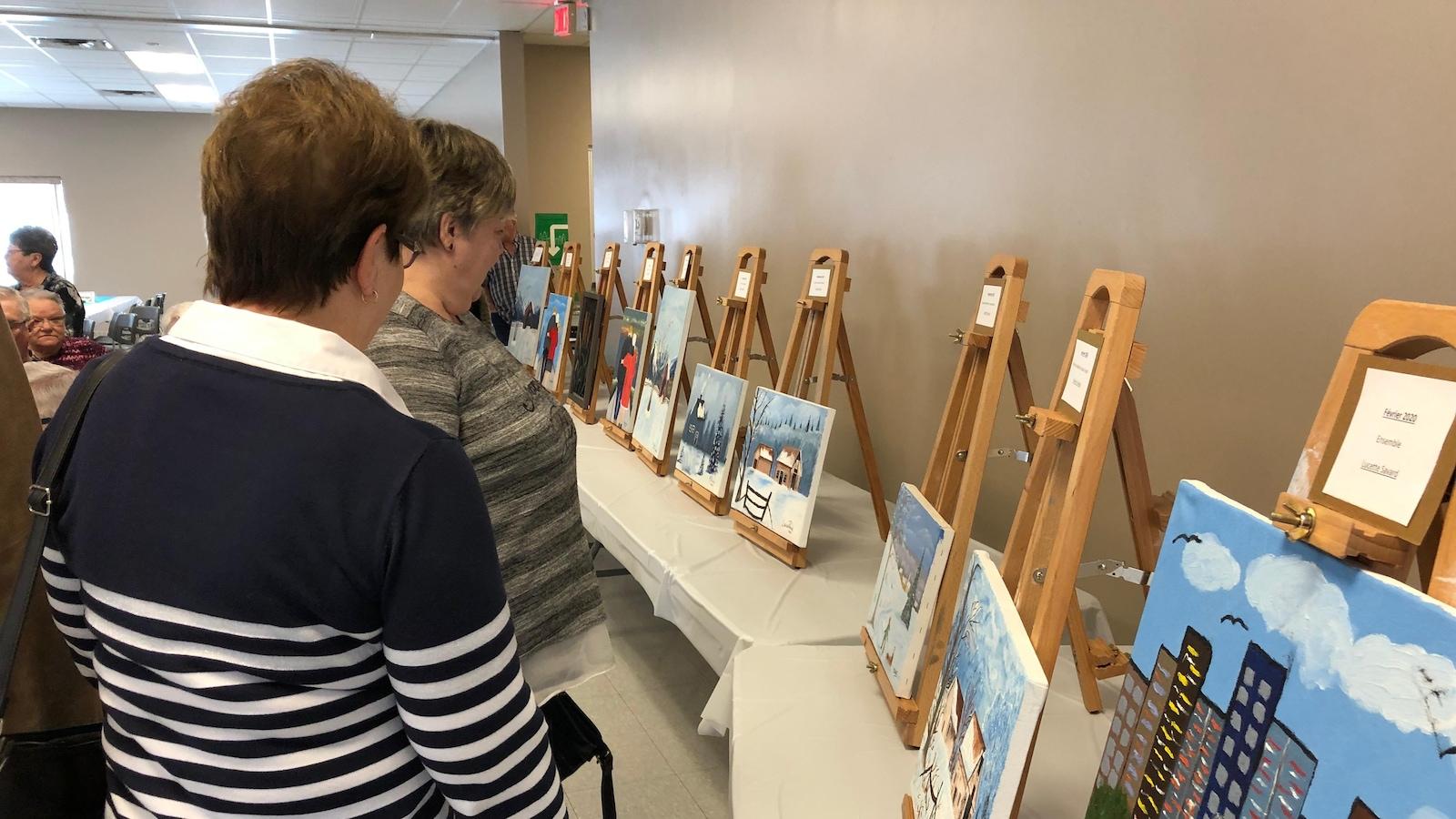 Des dames âgées regardent des tableaux