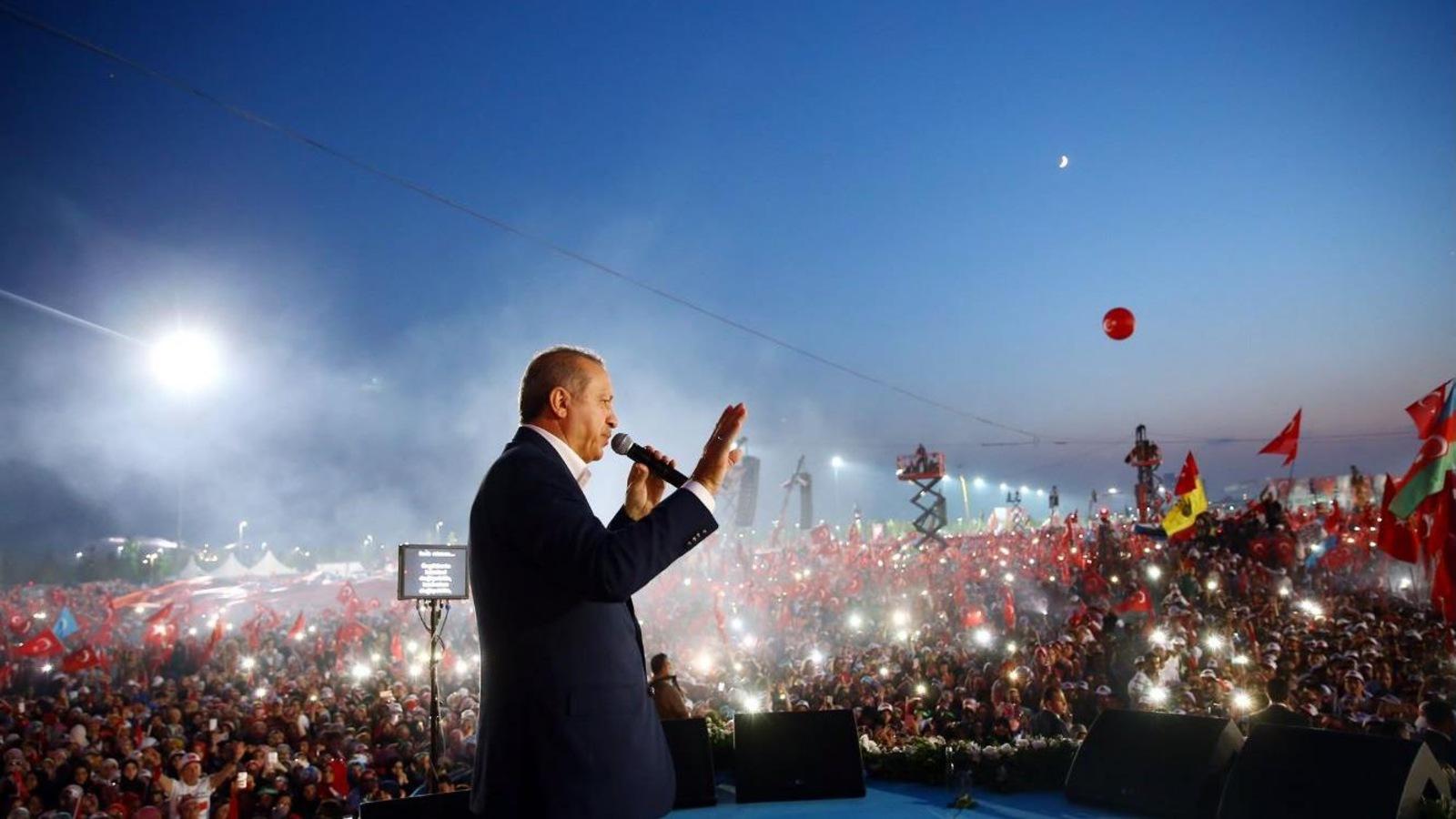 Recep Tayyip Erdogan regarde au loin, un micro dans la main gauche, la main droite levée pour saluer la foule.