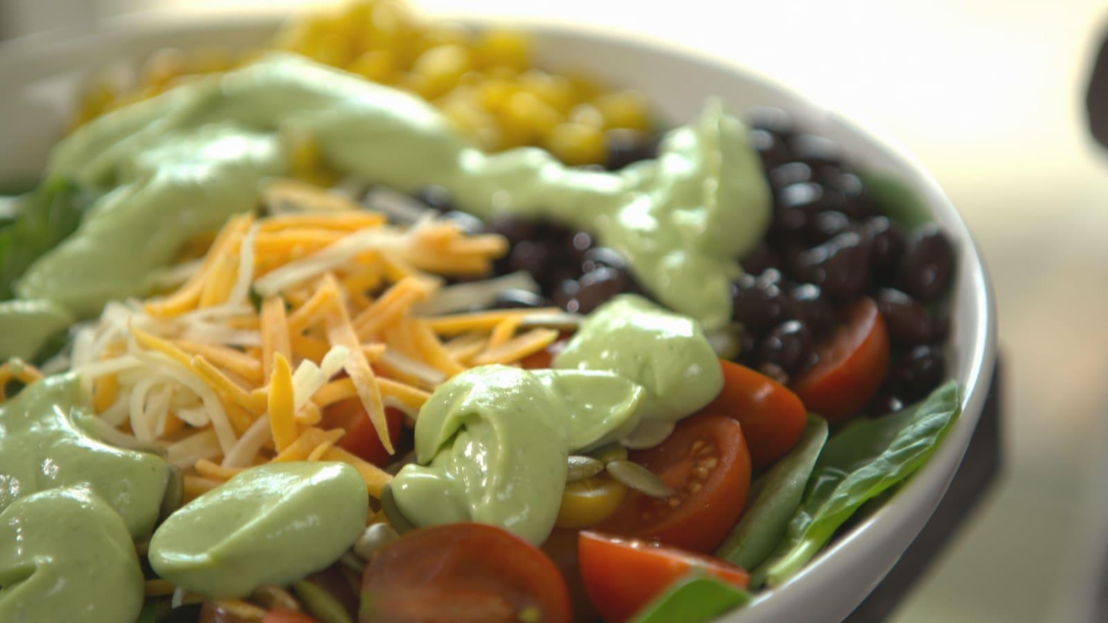 Un bol de salade avec de la vinaigrette à l'avocat.
