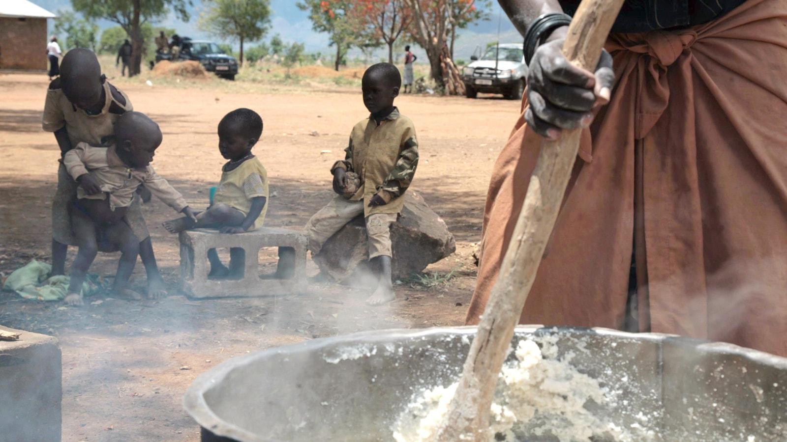 En Ouganda, une femme prépare un repas pour ses enfants.