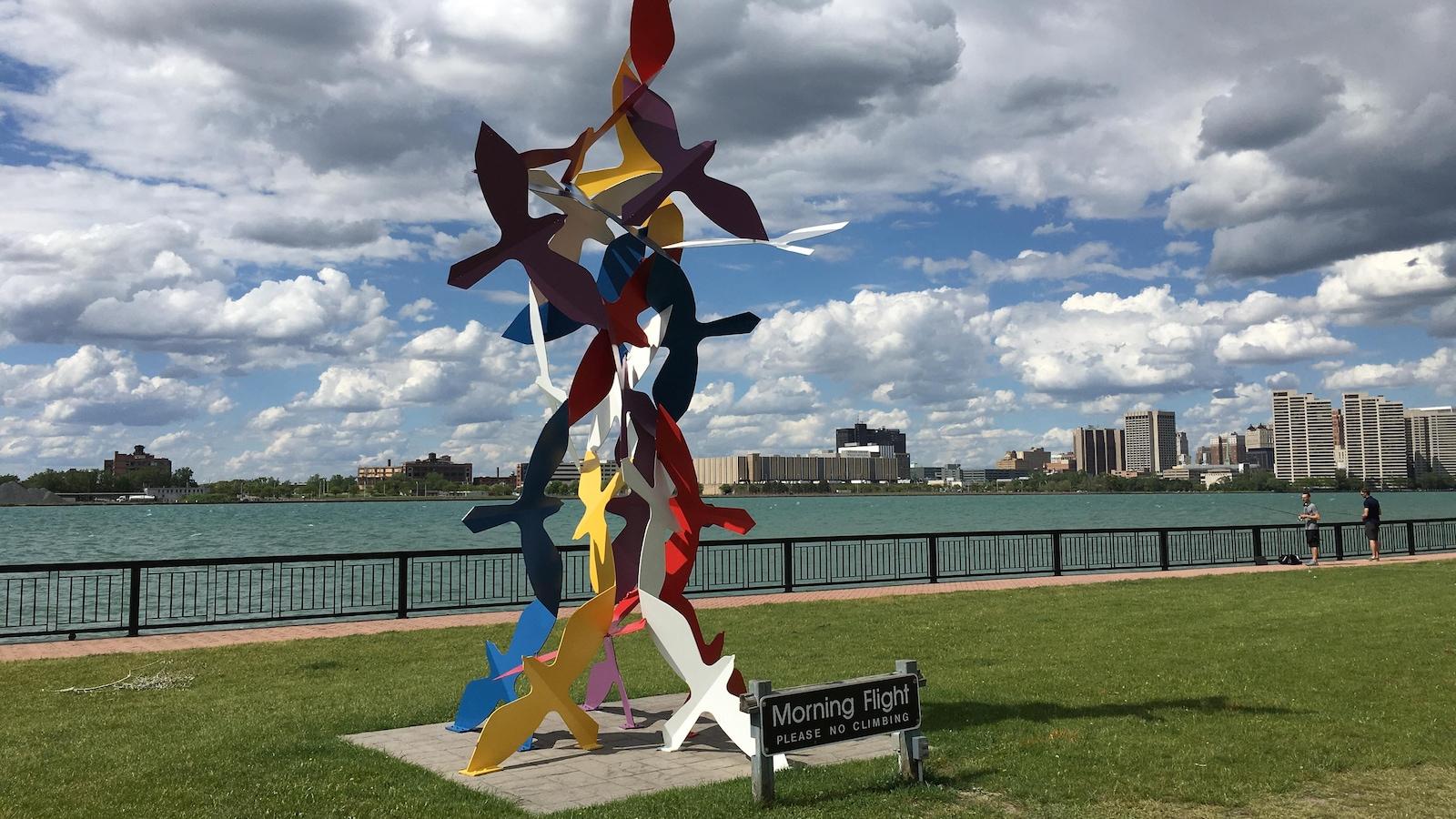 Installation artistique qui représente des oiseaux en vol sur le bord d'une rivière