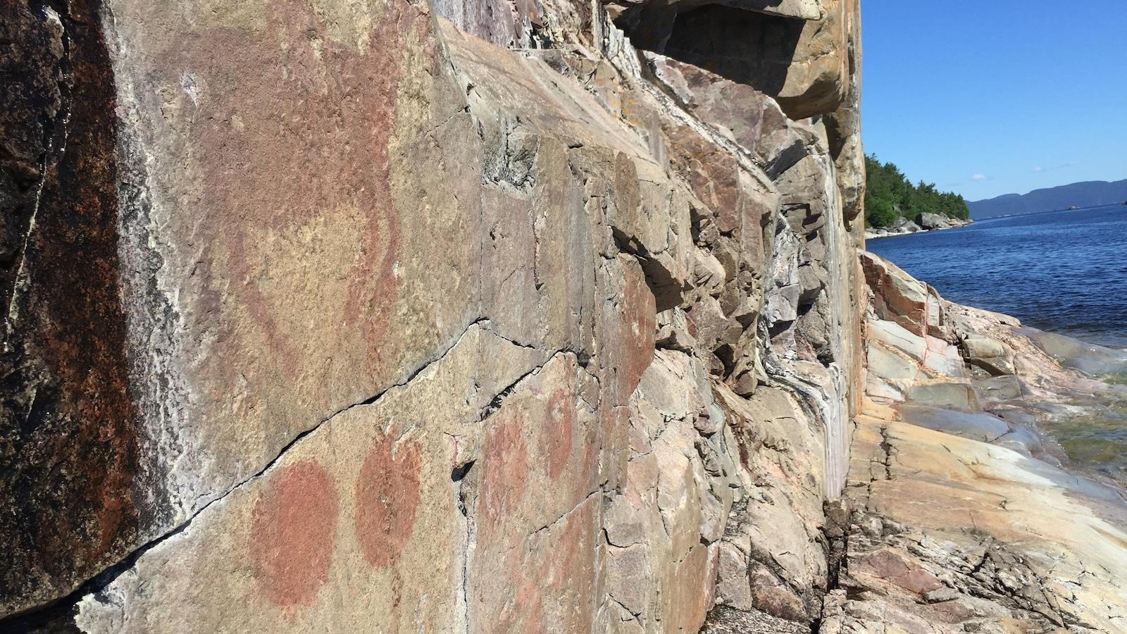 Pictogrammes peints à l'ocre rouge sur le rocher abrupt qui plonge dans l'eau