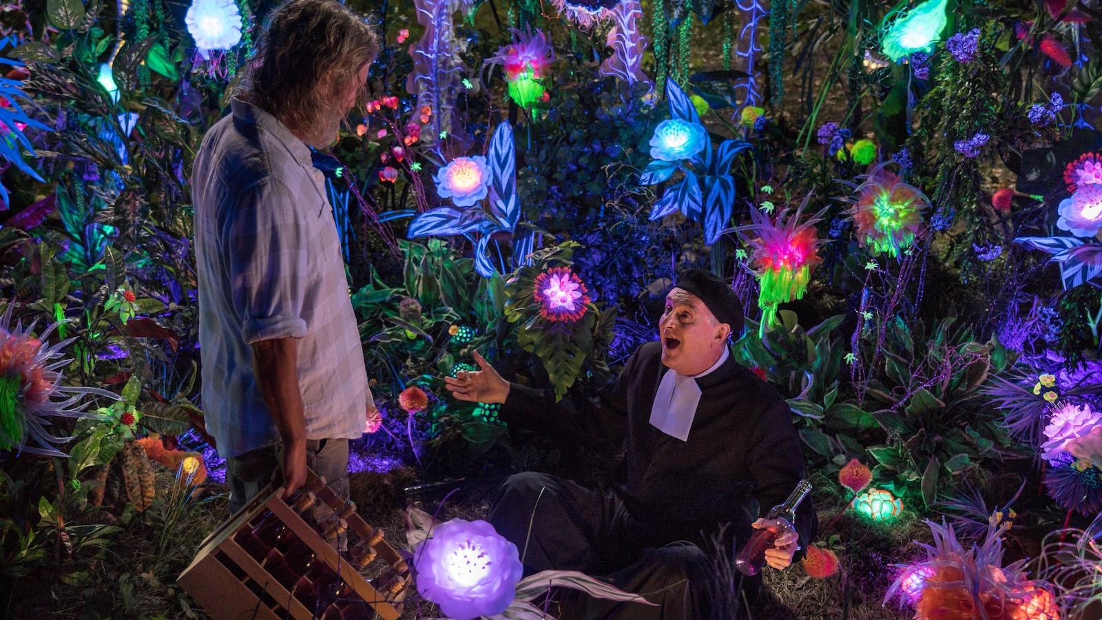 Les deux hommes sont dans un jardin de fleurs illuminées.
