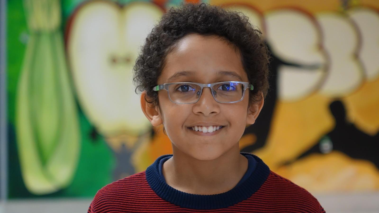 Un petit garçon portant des lunettes sourit à la caméra.