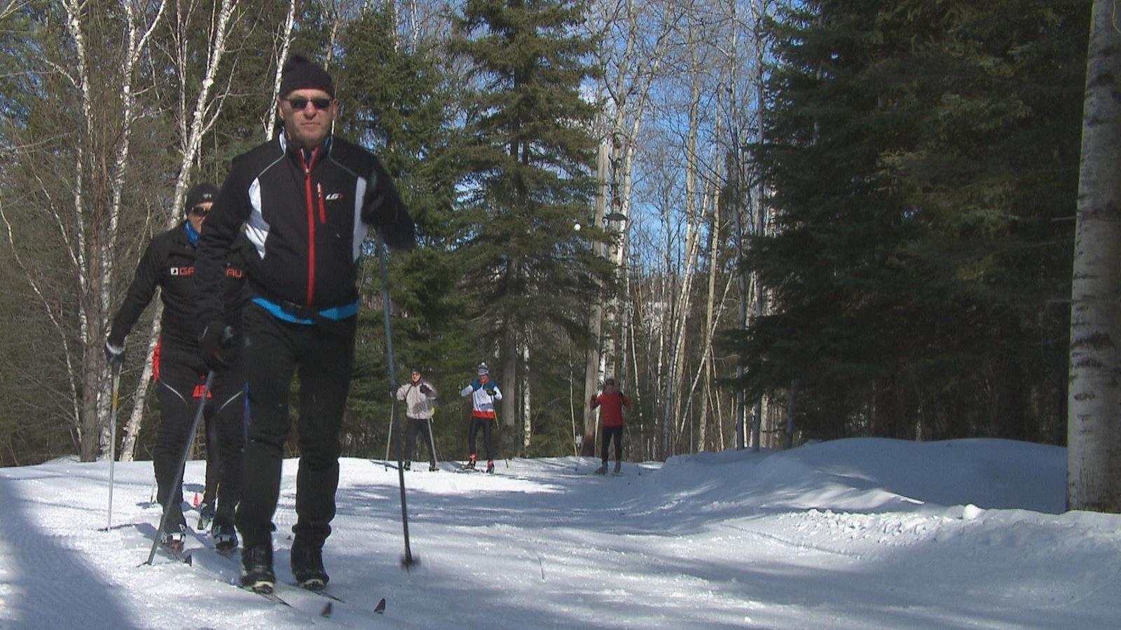 Des hommes en ski de fond dans un sentier