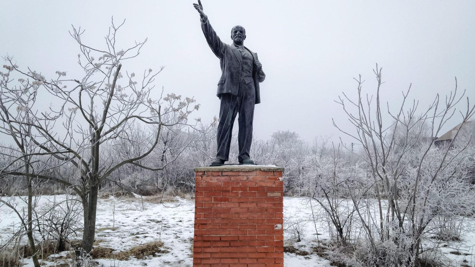 Une statue de Lénine dans un champ enneigé.