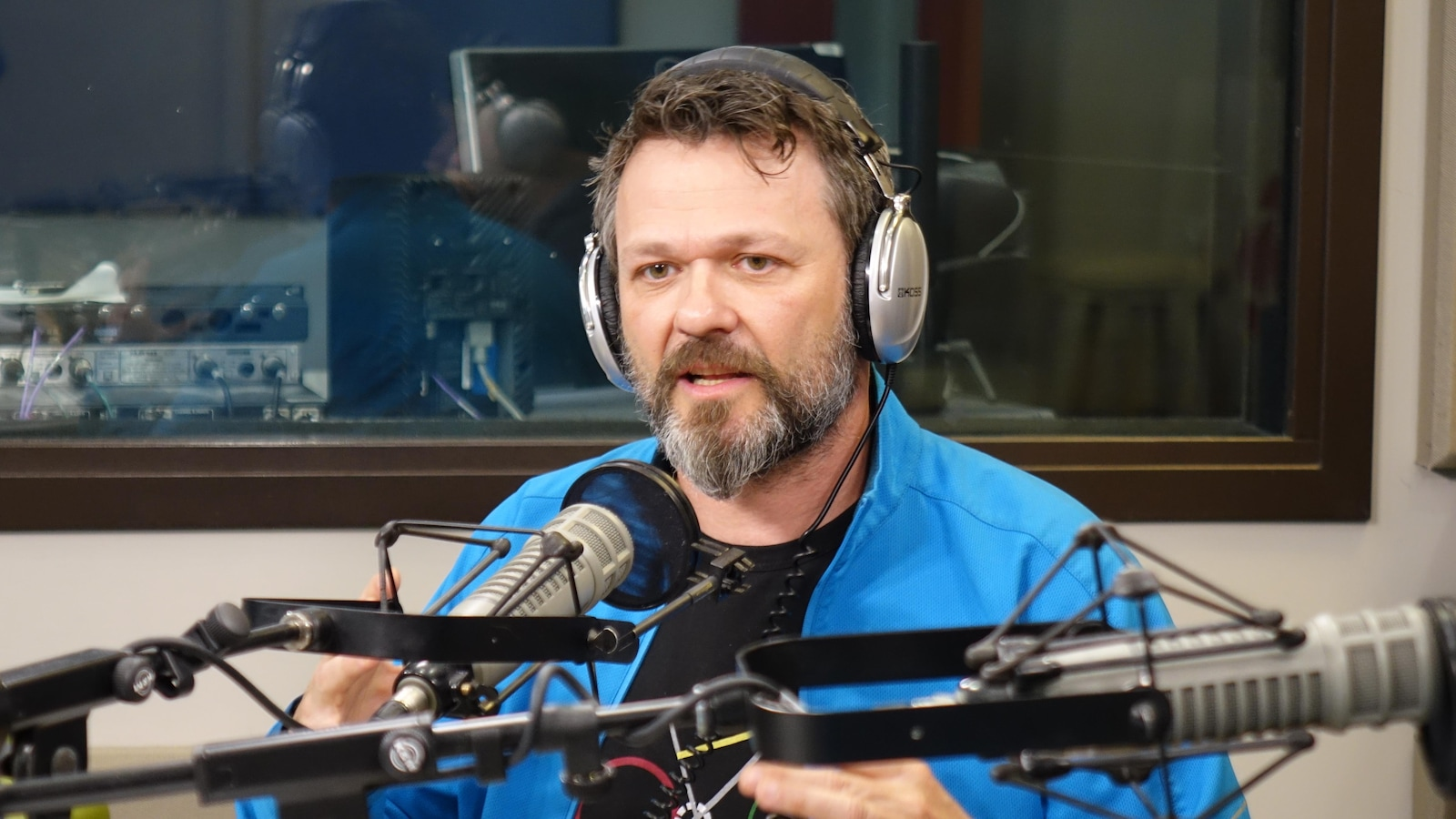 un homme parle au micro d'un studio de radio.