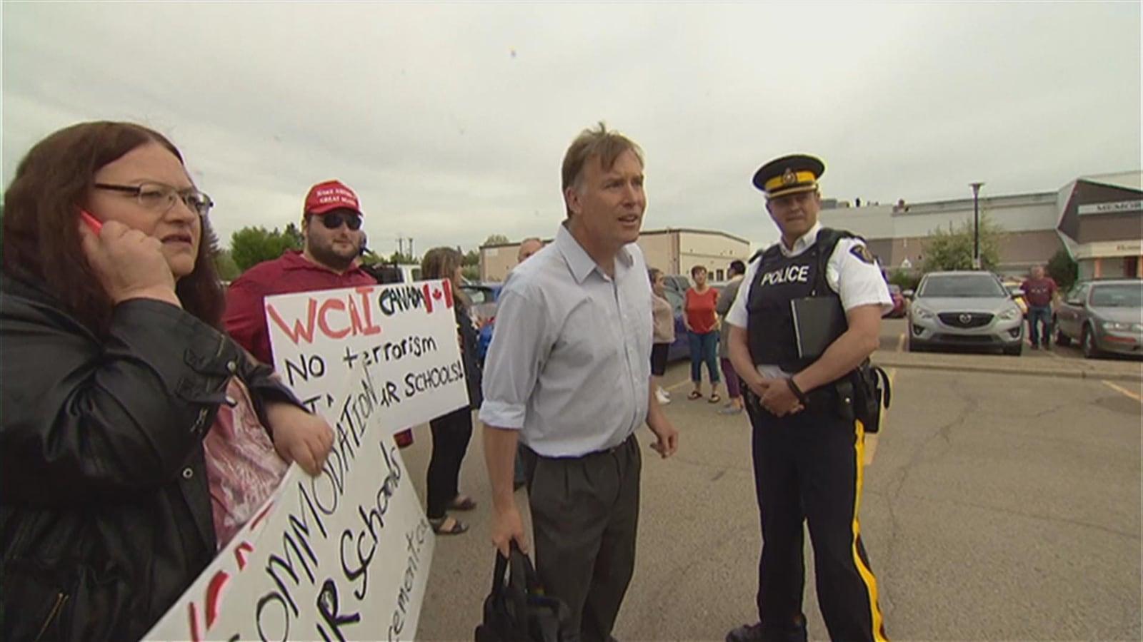 Début d'une manifestation avec des pancartes et un agent de police