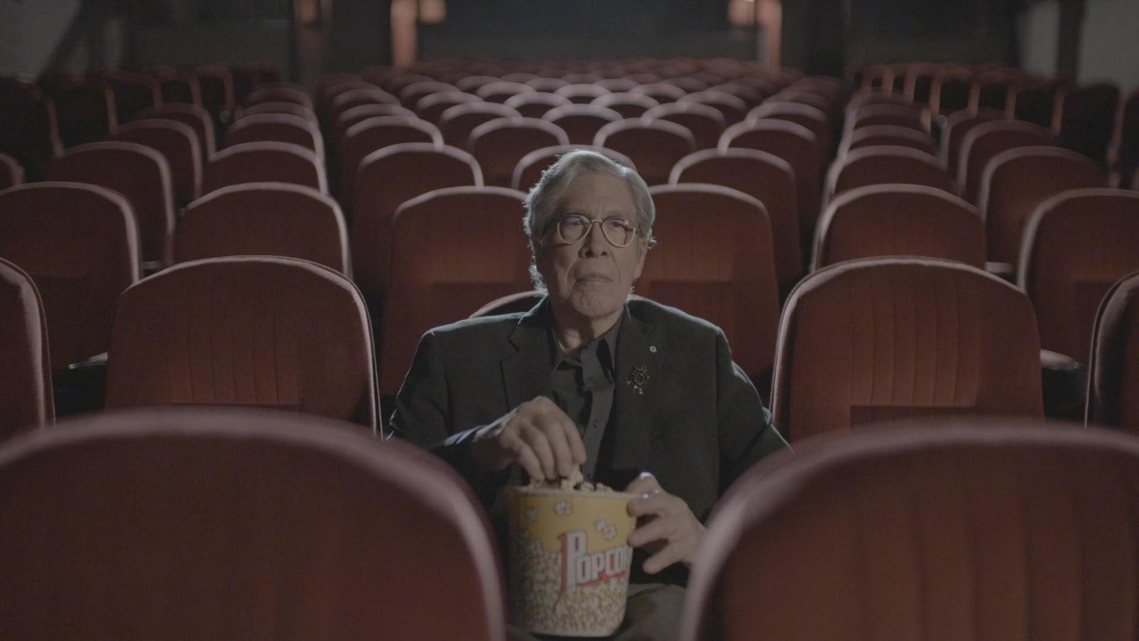 L'auteur Thomas King est dans une salle de cinéma vide et tient un pot de maïs soufflé.