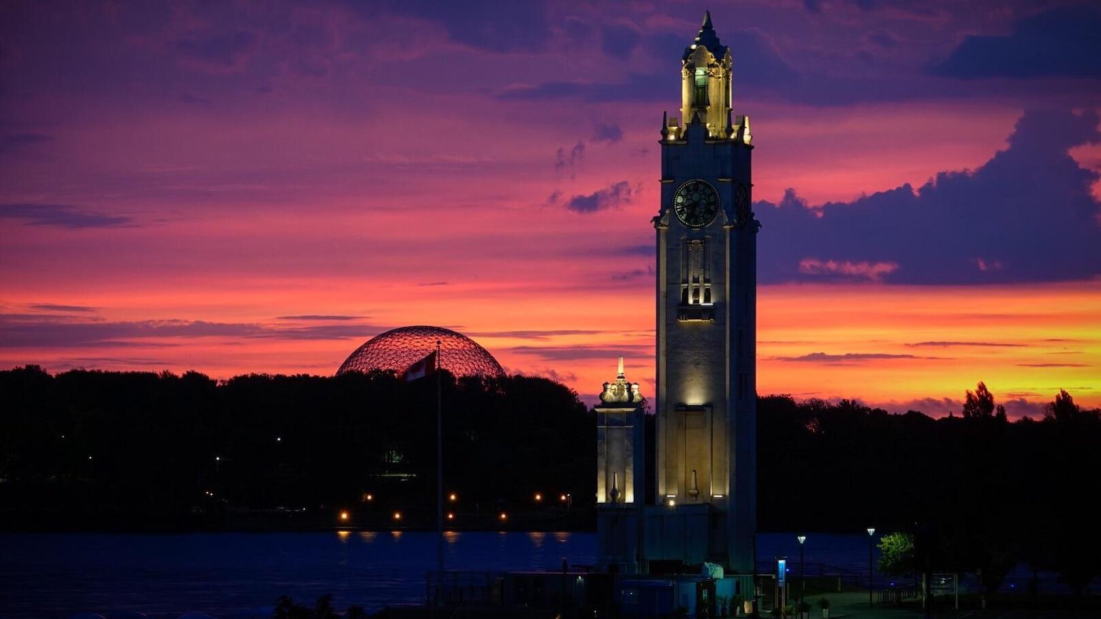 La tour de l'Horloge, au Vieux-Port de Montréal, à l'aube, devant la Biosphère au parc Jean-Drapeau.