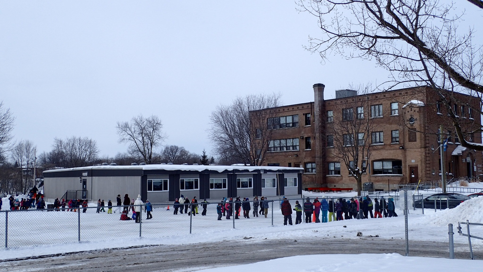Une cour d'école en hiver avec quelques dizaines d'enfants
