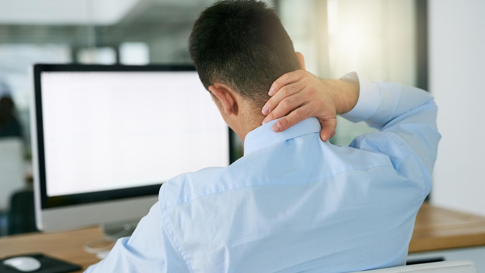 Un homme éprouve de la douleur au cou devant son ordinateur.