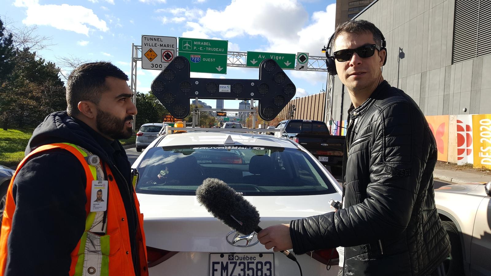 Un homme portant un dossard orange parle dans un micro tenu par un autre homme derrière une voiture portant un panneau lumineux stationnée dans une rue passante.