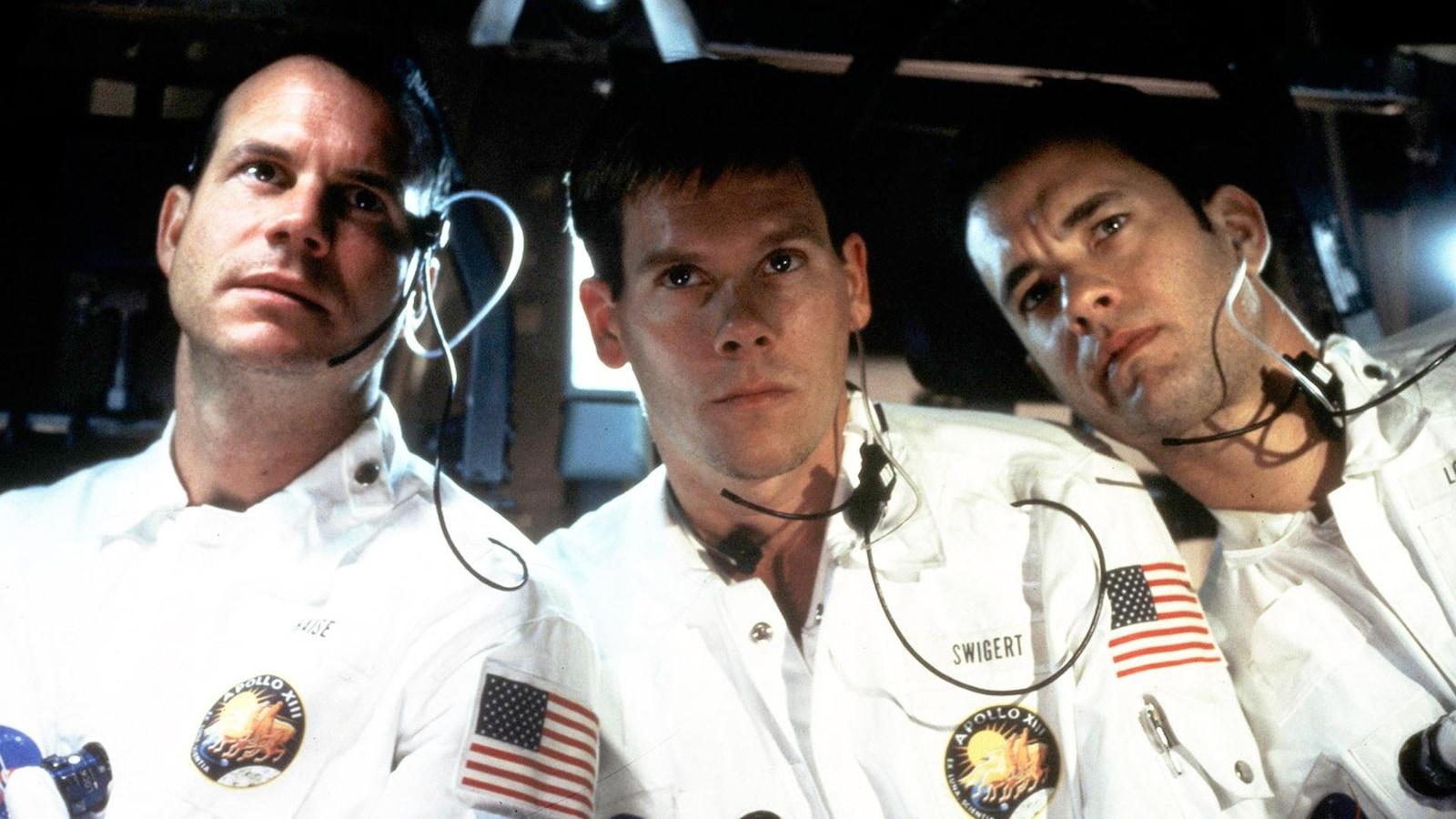 Trois hommes vêtus d'uniformes blancs dans une navette spatiale.