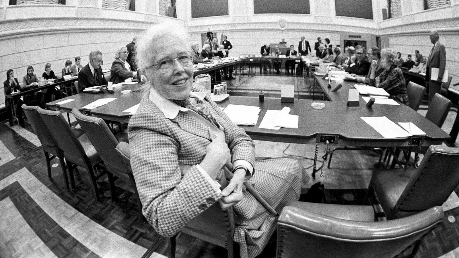 Photo en noir et blanc d'une femme âgée qui regarde la caméra dans une salle d'audience.