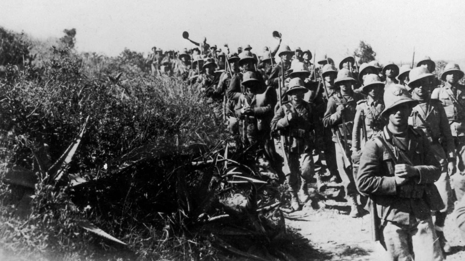 Photo en noir et blanc de soldats marchant près de buissons.