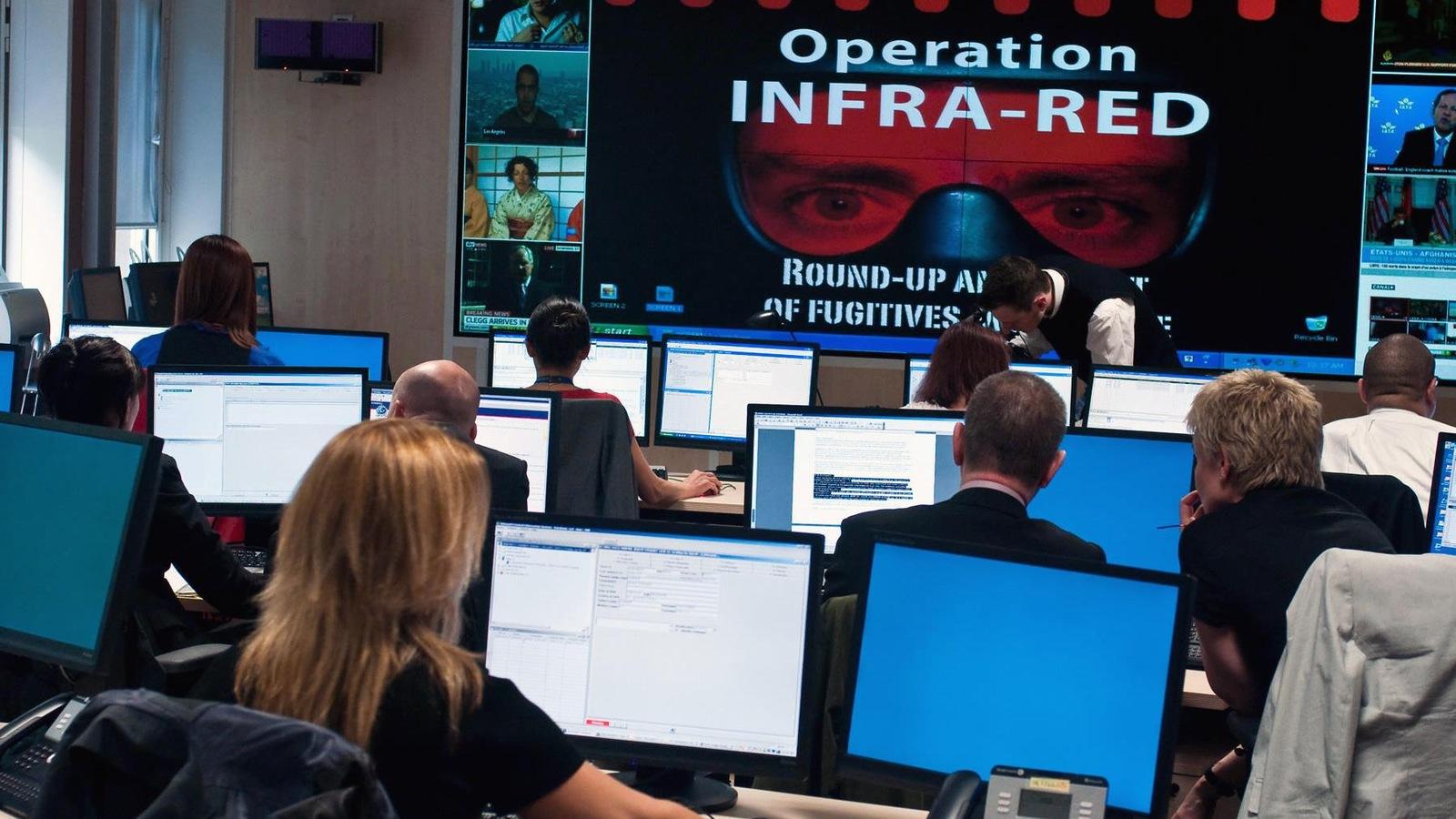 Dans une salle, des personnes travaillent sur des ordinateurs et devant un écran géant portant l'inscription Operation infra-red.