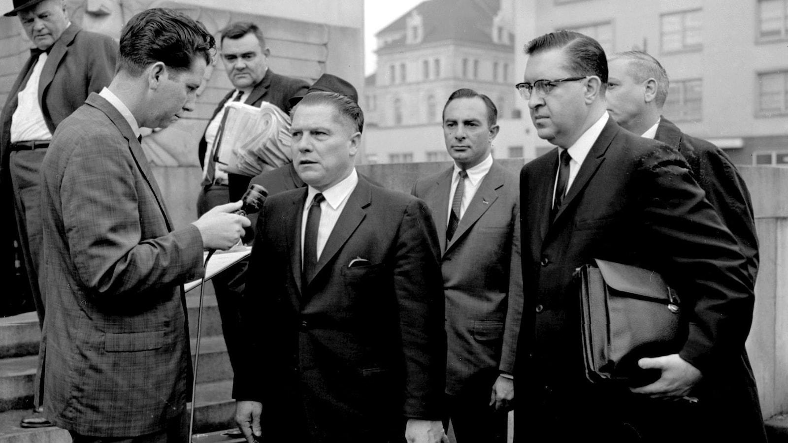 Un homme est interviewé par un journaliste qui tient un micro. Cinq autres hommes les entourent et les regardent.