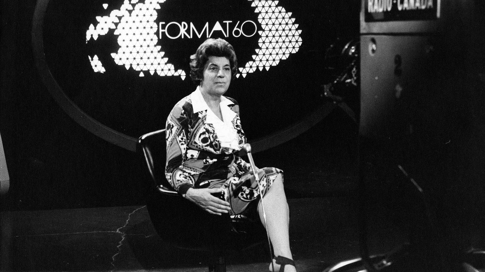 Photo en noir et blanc d'une femme assise sur le plateau d'une émission de télévision intitulé Format 60 et qui regarde une caméra de télévision.