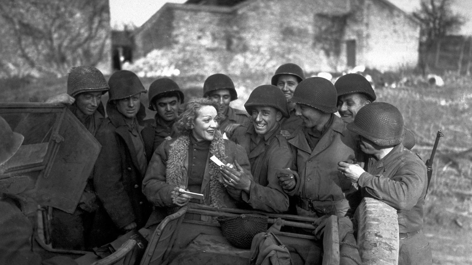 Photo en noir et blanc d'une femme entourée de soldats et qui donne une feuille de papier à l'un d'entre eux.