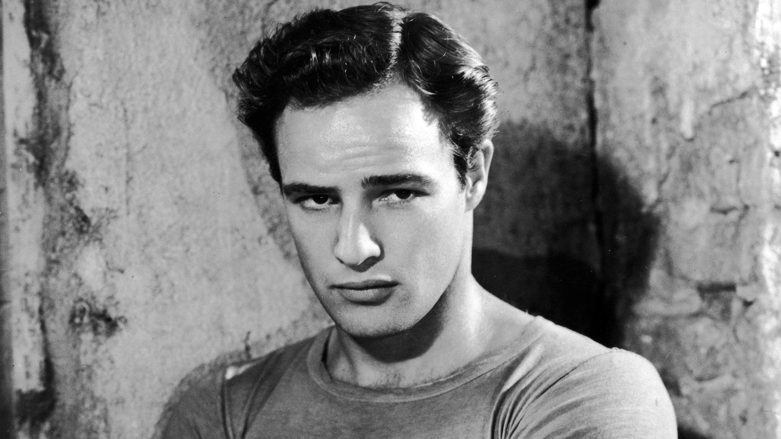 Photo en noir et blanc d'un homme qui regarde la caméra les bras croisés.