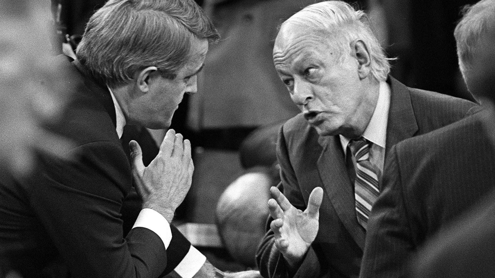Photo en noir et blanc de deux hommes qui se parlent d'assez près.