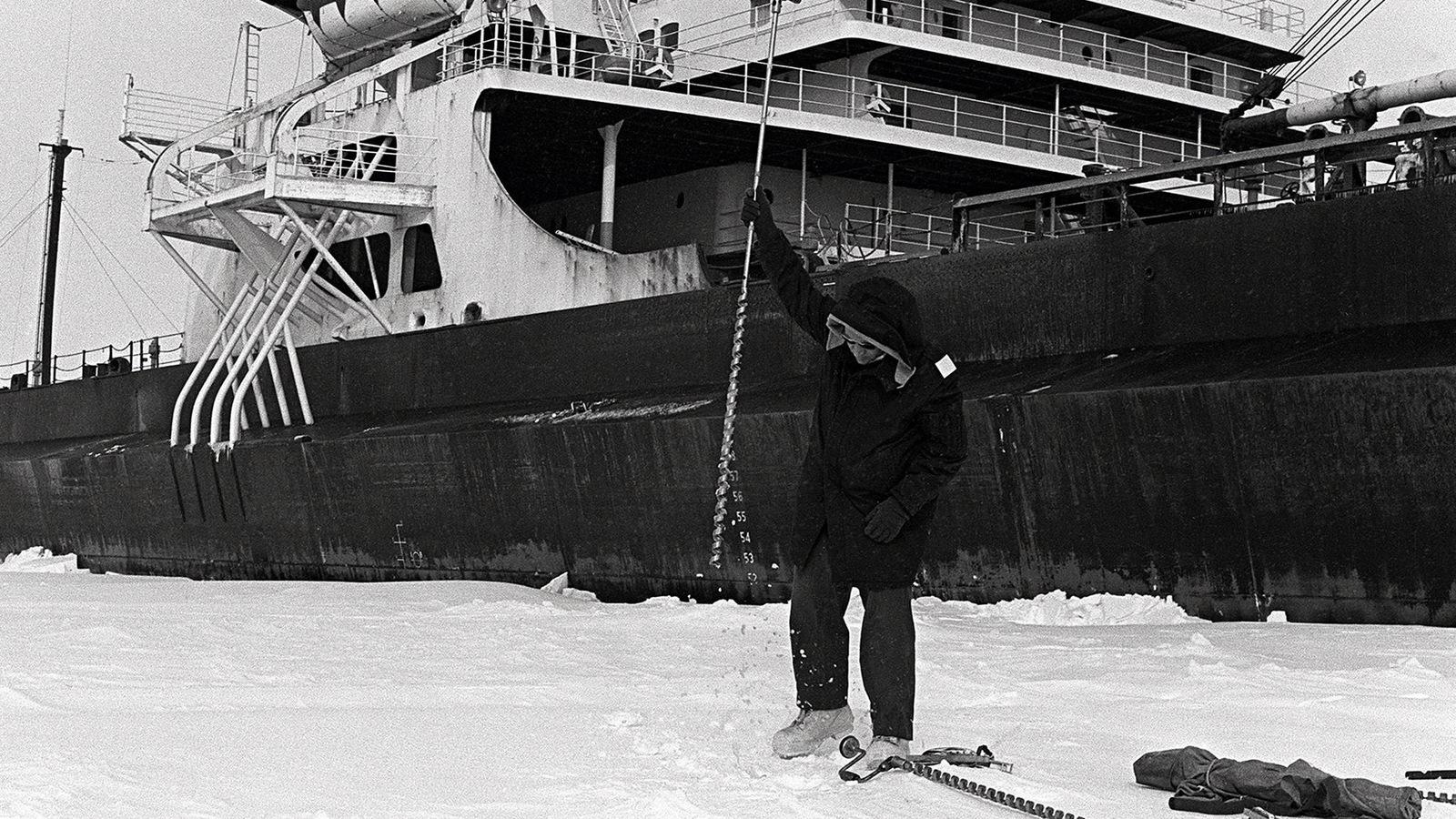 Photo en noir et blanc d'un homme qui lève un pic au-dessus de la glace alors qu'un navire se trouve derrière lui.