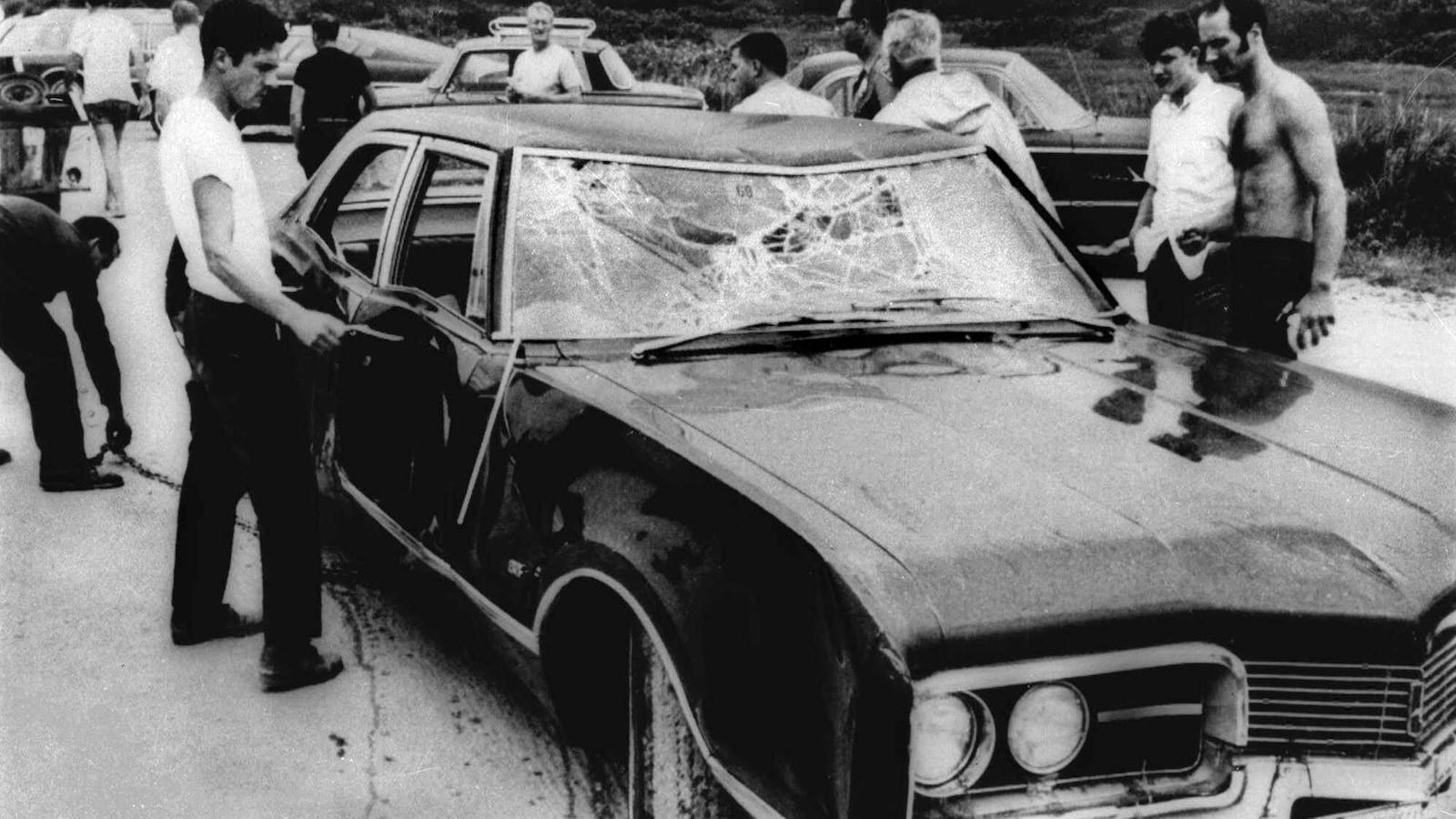 Photo en noir et blanc de trois hommes entourant une voiture accidentée.