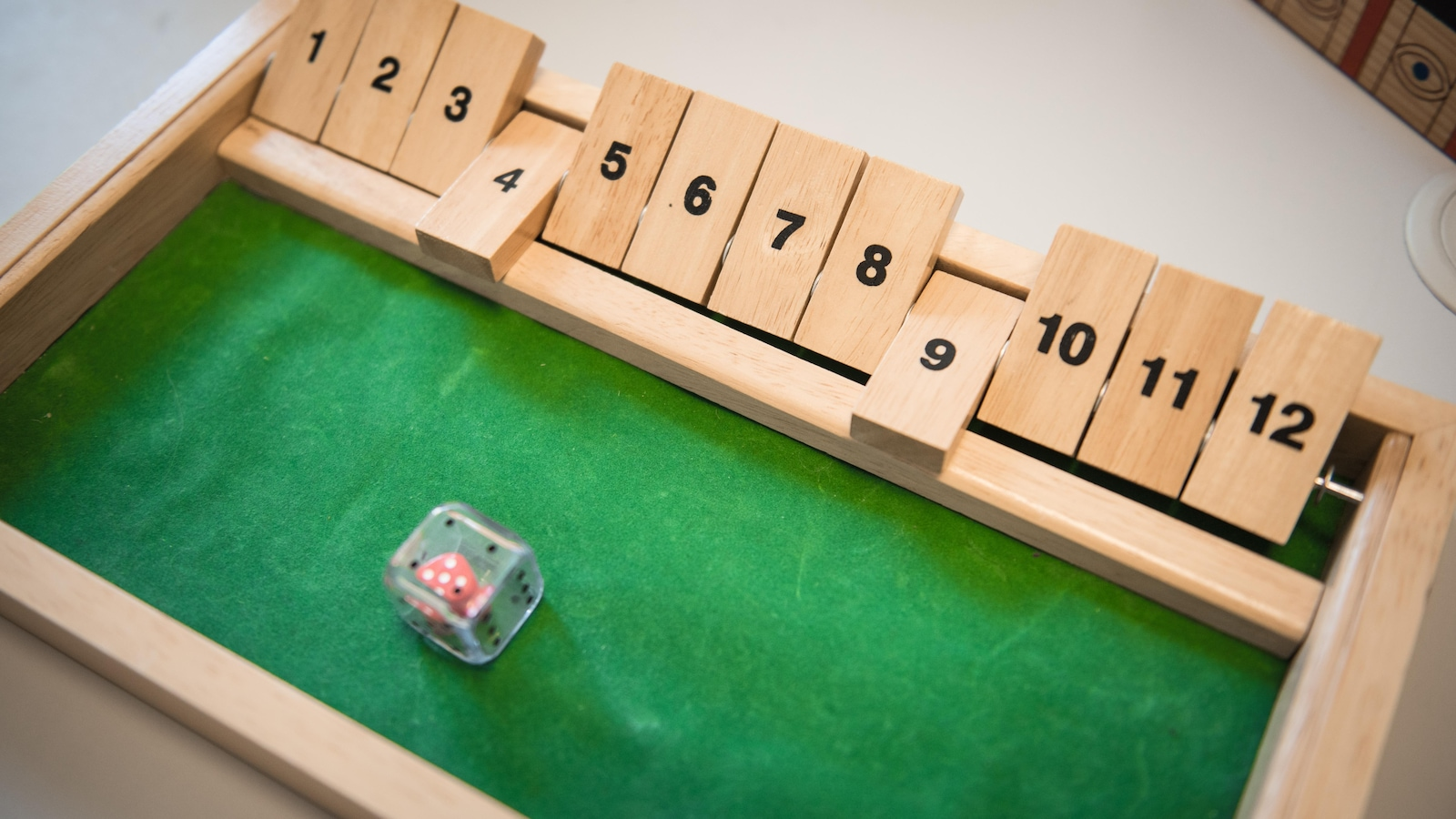 Une boite en boite au fond vert qui contient douze morceaux de bois alignés sur une tige de métal et un dés en plastique transparent avec un autre dé rouge à l'intérieur.