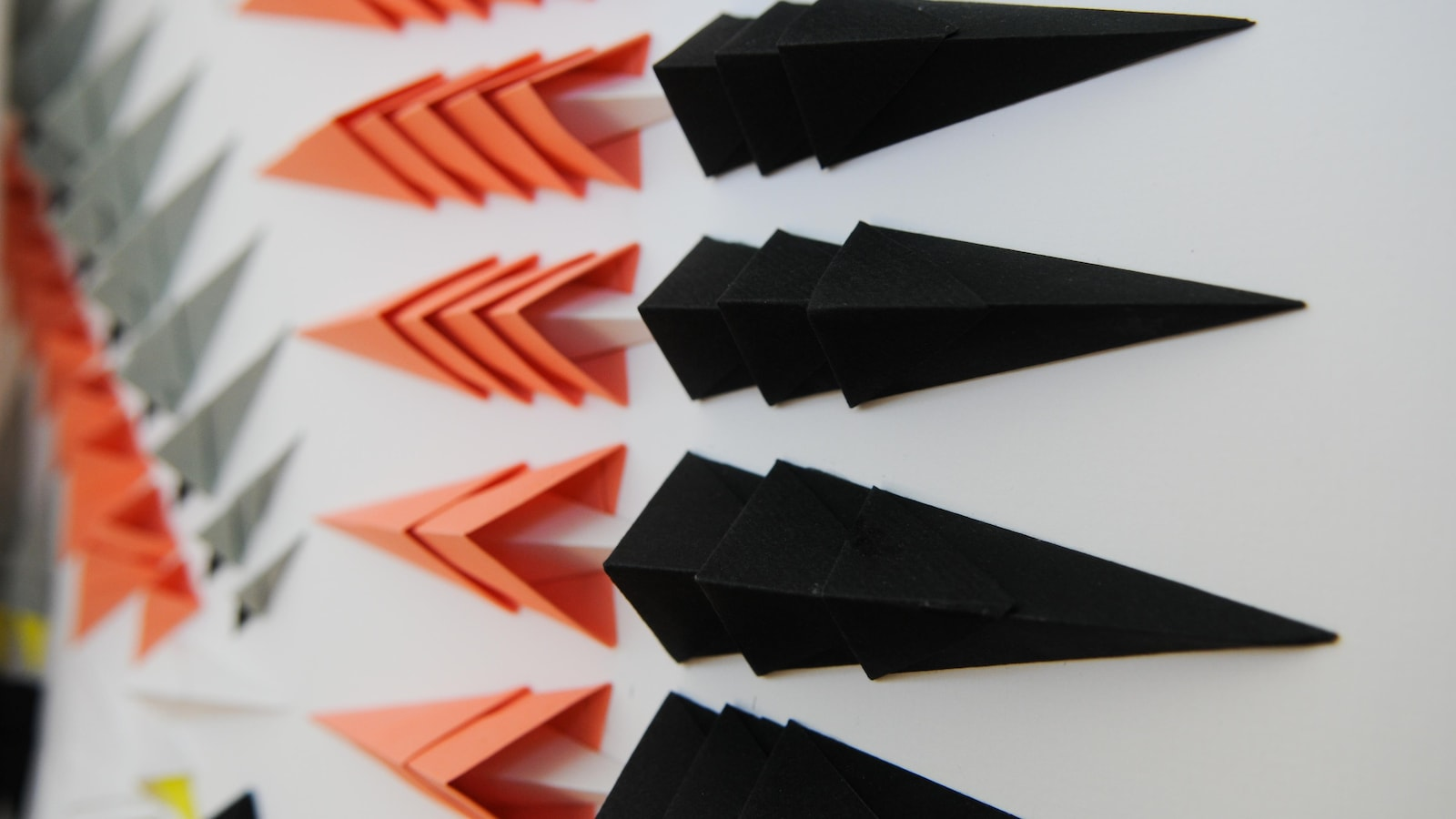 Plan rapproché sur une oeuvre montrant des morceaux de papiers pliés de couleurs noire, rose, gris et jaune.