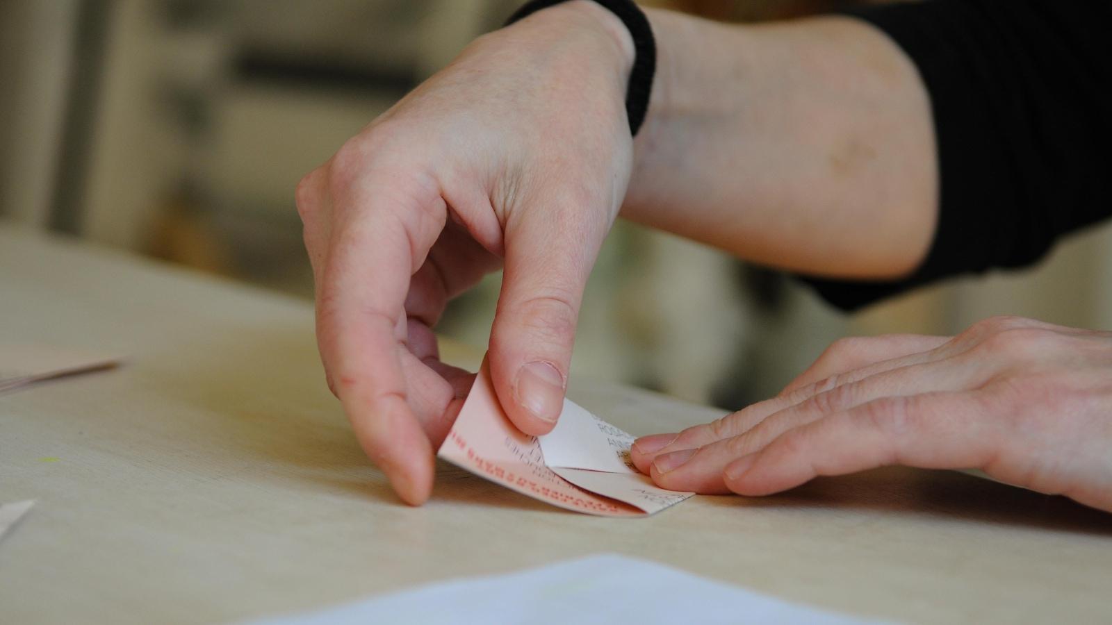 Plan rapproché montrant des mains en train de plier du papier en triangle.