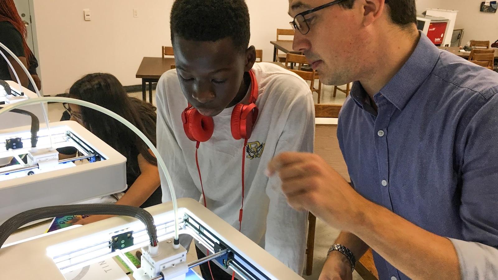 Le professeur et un élève devant une imprimante 3D.