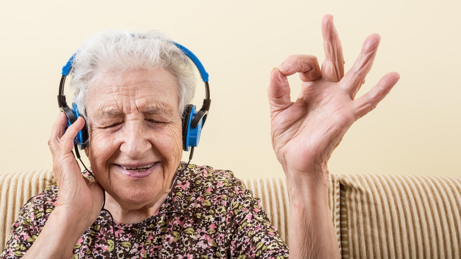 Une dame agée qui écoute de la musique avec un sourire au visage.