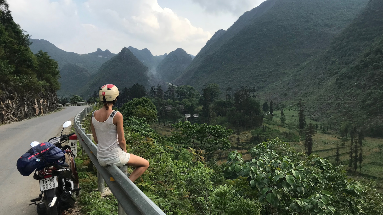 Une femme assise en bordure d'une route regarde un paysage.