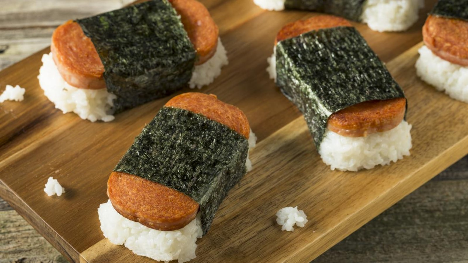 Quatre morceaux de musubi, un sushi fait avec du jambon en conserve Spam, sur une planche de bois.