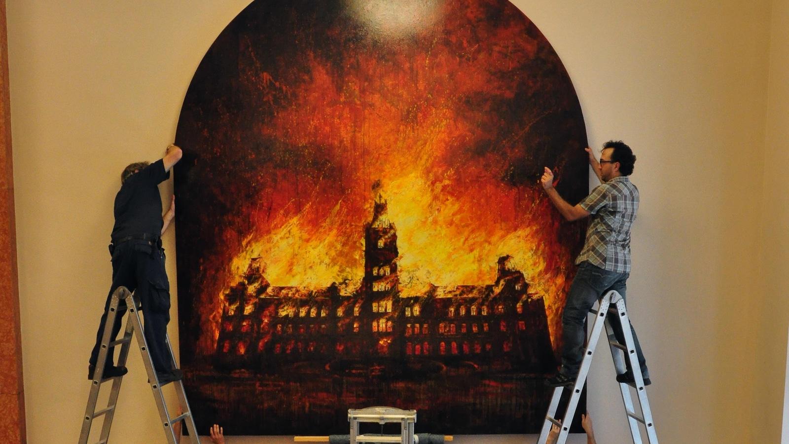 Cinq personnes et trois échelles entoure une toile installée sur un mur qui représente le parlement de Québec en feu.