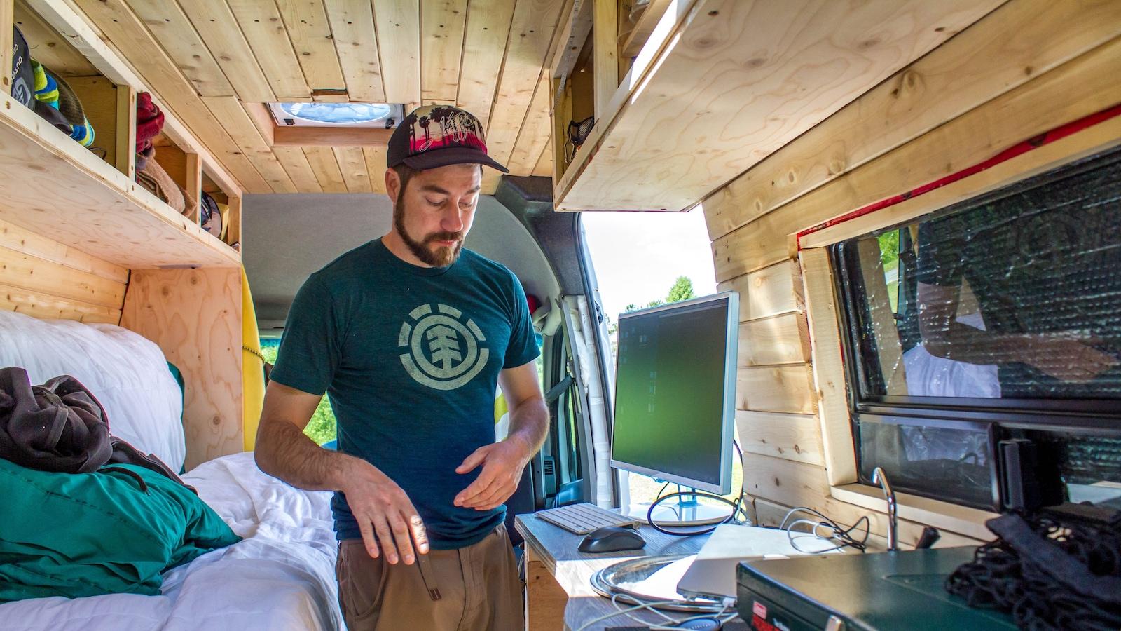 Un homme se trouve à l'intérieur d'une fourgonnette entièrement aménagée pour y vivre au quotidien. On y voit un lit, un évier et des armoires.