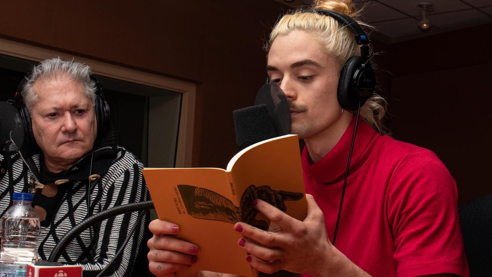 Cheveux décolorés, le poète lit dans son recueil à la couverture orangée.