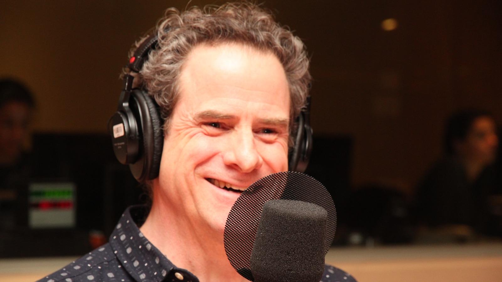 L'homme sourit. Il est assis dans un studio de radio devant un micro et il porte des écouteurs.
