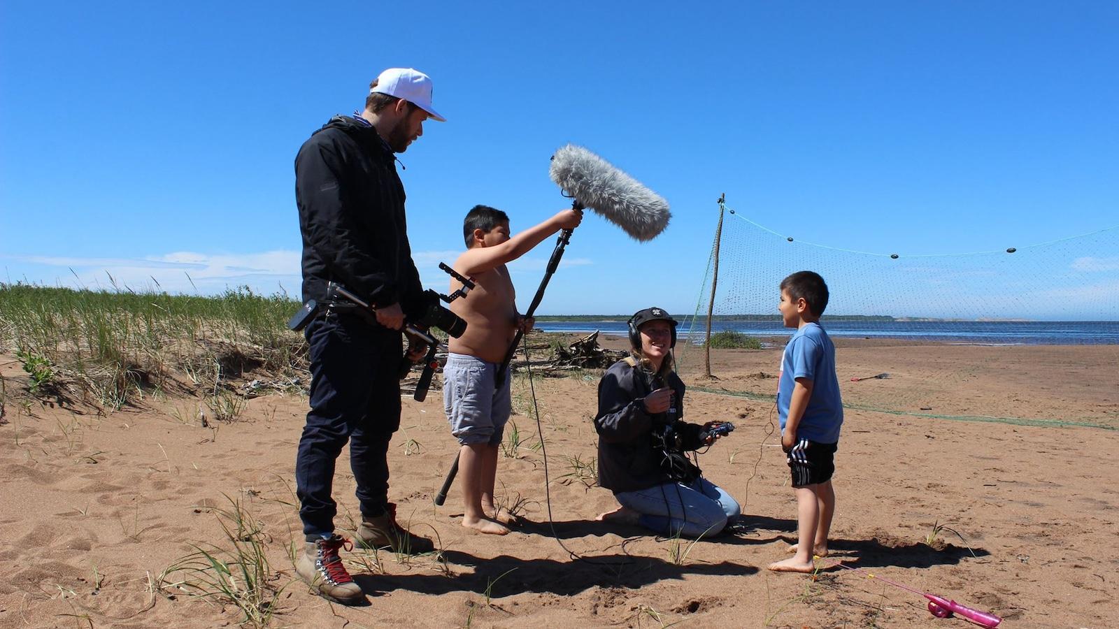 Équipe du Wapikoni mobile sur la plage à Nutashkuan avec deux enfants innus