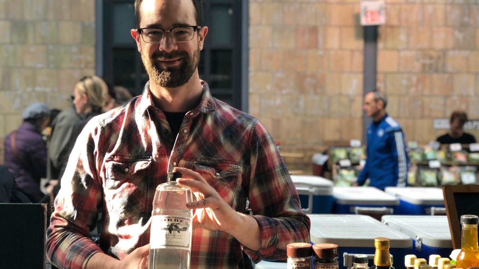 Dyson Forbes, de Forbes Wild Foods pose avec une bouteille de sève de bouleau.