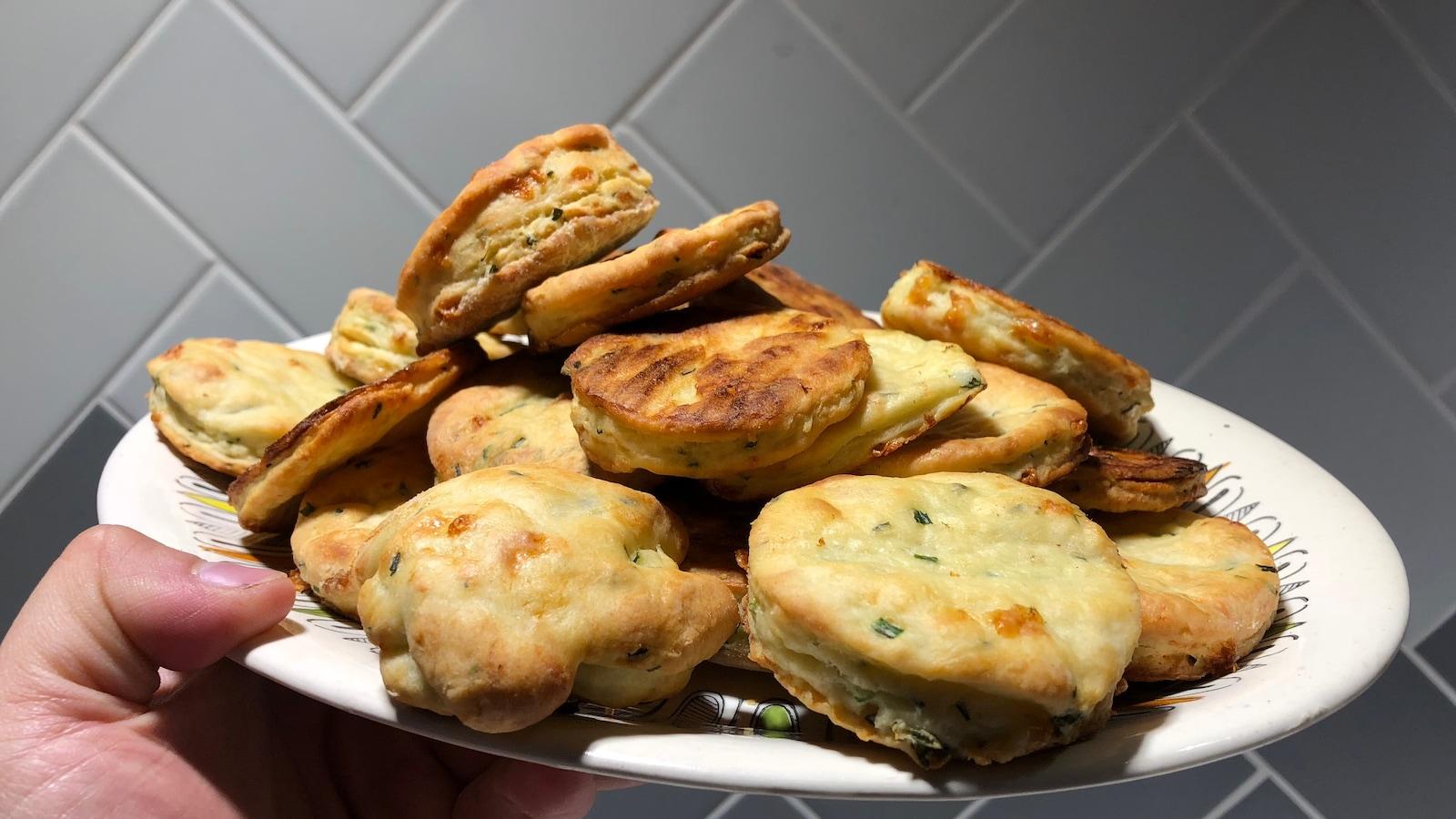 Des scones au fromage et à la ciboulette dans une assiette.